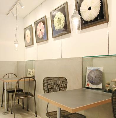 客席 : 厨房前のお席です。少し無骨な椅子、照明、そしてテーブル横の展示をお楽しみください。
