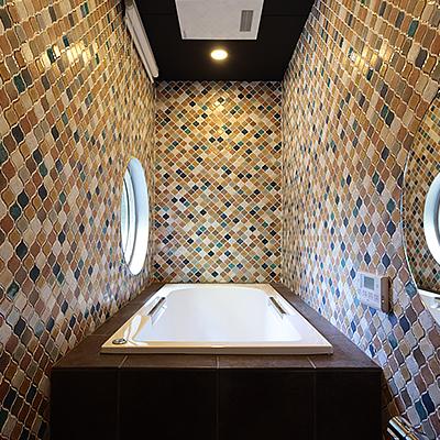 浴室 : カラフルなタイル貼りの浴室です。丸窓から庭の景色を眺めながらご入浴していただけます。